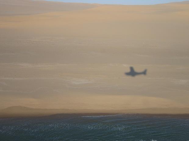 Flugzeug vor der Kulisse von Dünen und Atlantik