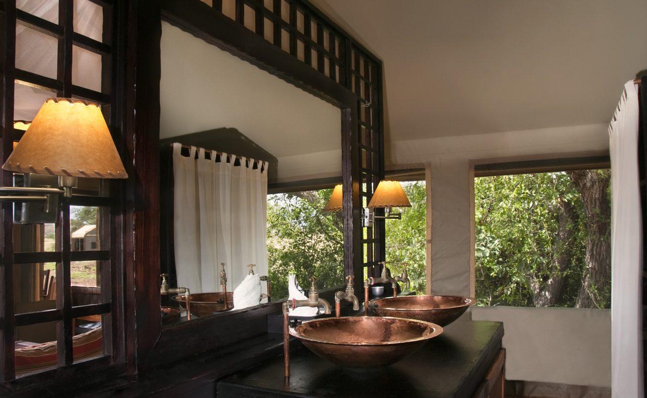 Luxusbadezimmer mit Kupferwaschbecken im Desert Rhino Camp